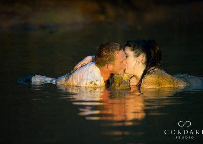 couple pashing in mud pool