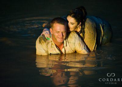 Belinda whispering to Dan in mud