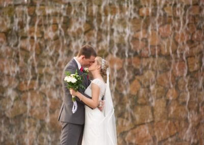Bride and groom kissing by waterfall