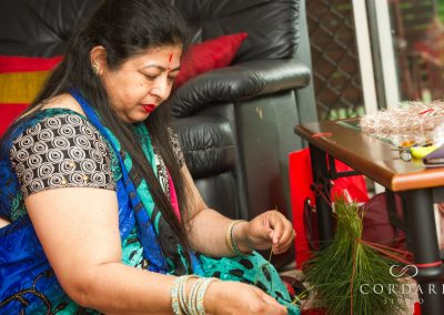Aunty making grass necklace